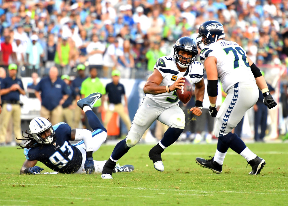 Seattle Seahawks quarterback Russell Wilson (3) escapes a sack from Titans outside linebacker Kevin Dodd (93) in the second half of the Seahawks at Titans NFL football game on Sept. 24, 2017, at Nissan Stadium in Nashville, Tenn. The Titans won 33-27. (Photo by Lee Walls / Walls Media)