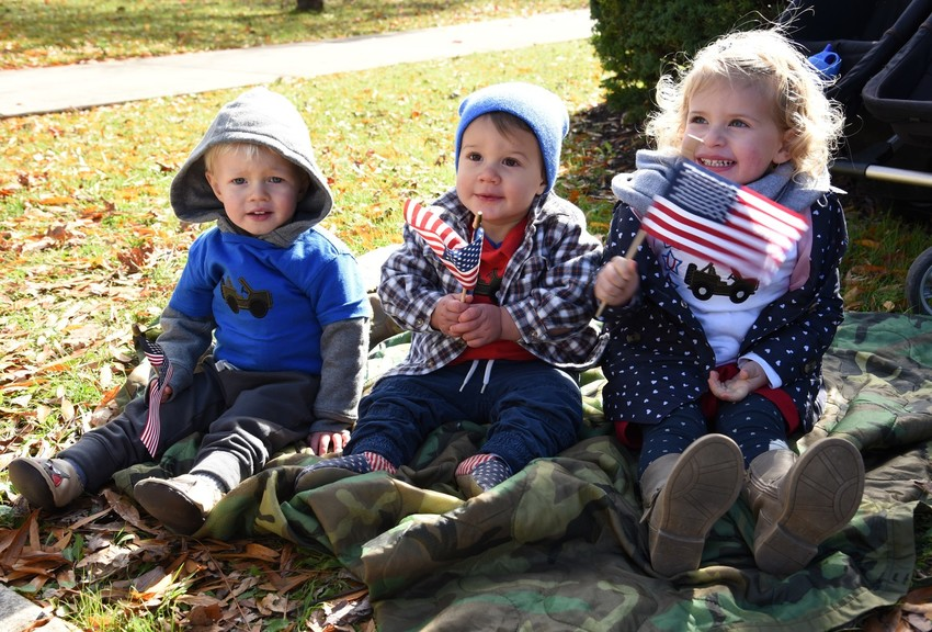 Youngsters Fletcher Johnson, the two-year-old son of Alane and Micah Johnson of Cookeville, and Mickey and Ruby Boyd, the 17-month-old son and two-year-old daughter of Matthew and Angela Boyd of Cookeville, anxiously await the start of the Veterans Day Parade while sitting on a U.S. Army poncho liner at the courthouse square in downtown Cookeville.