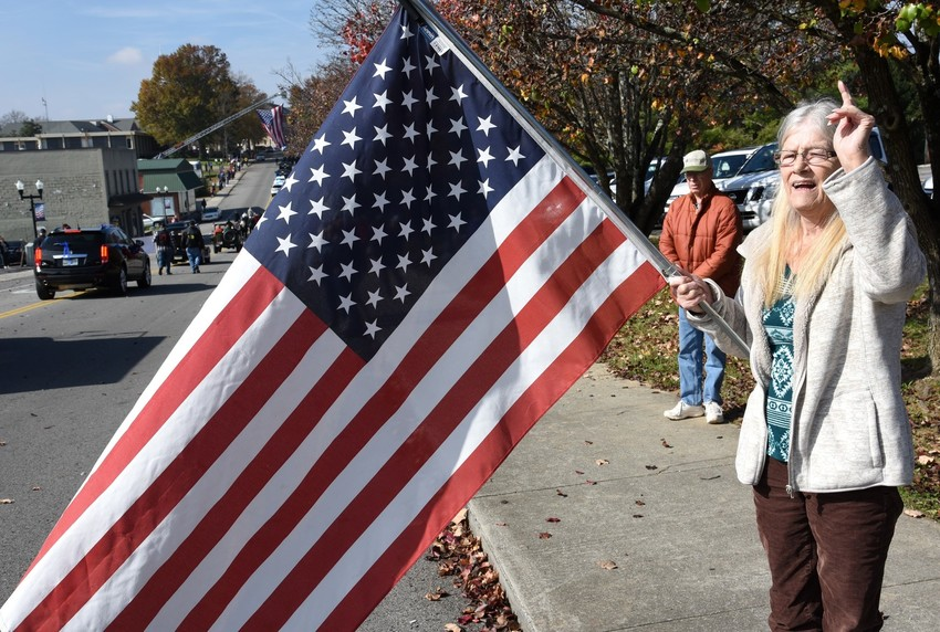 "Nancy Swenson, a self-proclaimed 65-year-old U.S. Navy brat, shouts out ""thank your"" to the men and women participating in the Veterans Day Parade and to all veterans."