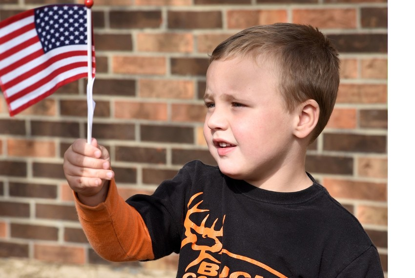 Three-year-old Peyton Hawkins of Livingston waives the American Flag.