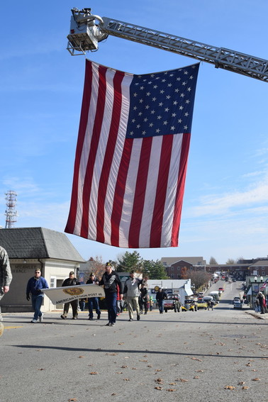 American Legion Post 46 marches in Friday's Veterans Day Parade under an American flag hanging from a Cookeville Fire Department truck on Broad Street.