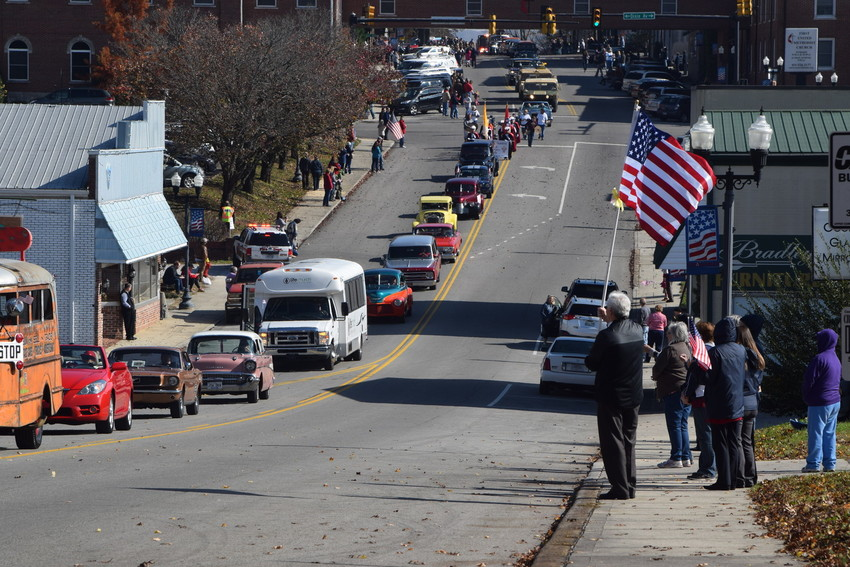 A man holds an American flag as cars parade down Broad Street.