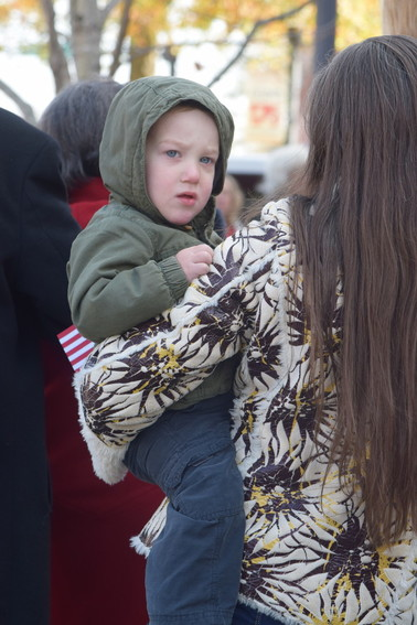 Two-year-old Ephraim, held by his mother, Mary Brenneman, during the Veterans Day ceremony outside the Putnam Courthouse.
