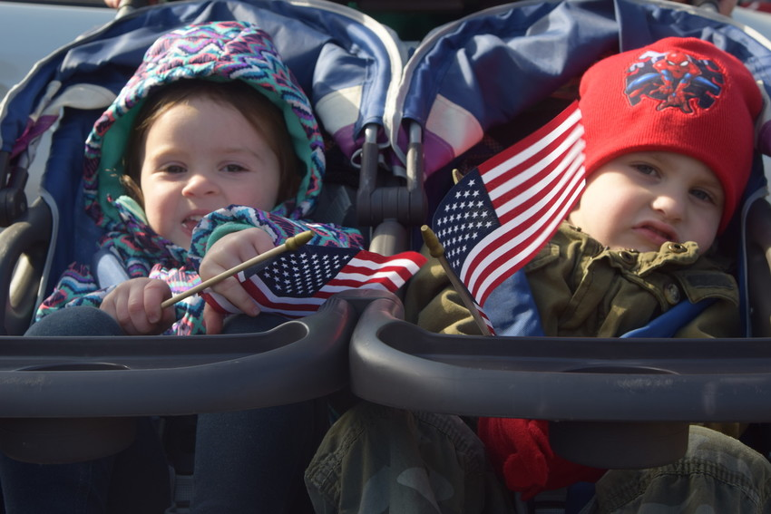 Two-year-old Nora Miller and three-year-old Judah Coburn hold flags as they watch the Veterans Parade from the comfort of a double stroller Friday.