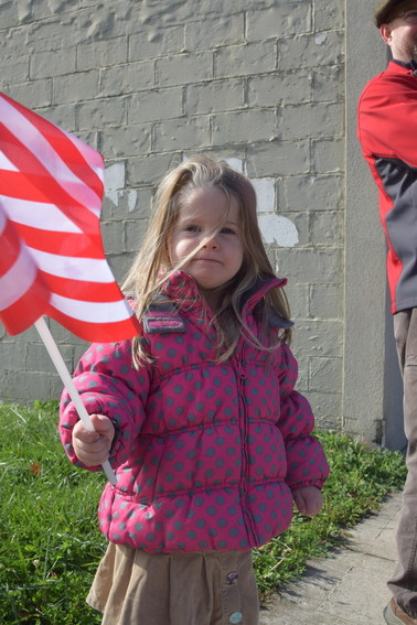 Three-year-old Elena Yarbrough holds a flag as she watches the parade on Broad Street.
