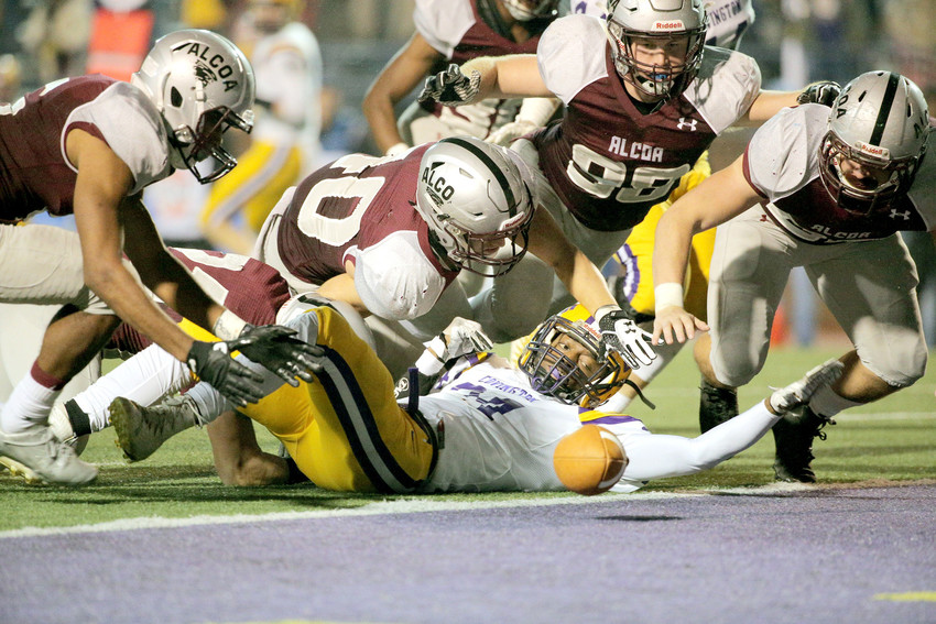 Alcoa High School's Davis Maples (40) and Gary Carroll (98) dive over a Covington player for a loose ball during the Class 3A championship game Thursday at Tucker Stadium on the Tennessee Tech campus. Alcoa won by a score of 31-20