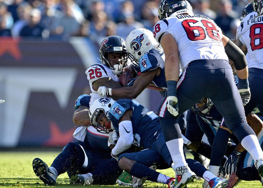 Houston Texans running back Lamar Miller (26) is tackled in the first half of the NFL football game between the Tennessee Titans and the Houston Texans on Dec. 3, 2017, at Nissan Stadium in Nashville, Tenn. The Titans won 24-13. (Photo by Lee Walls)