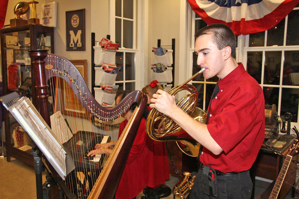 John McKeon of the McKeon Family plays a French horn at the Monterey Depot Museum after the Christmas parade on Saturday.