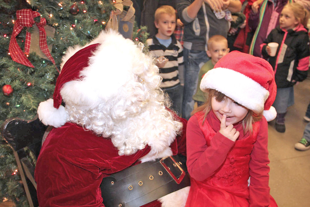 A little girl contemplates her Christmas wishes during a visit with Santa at the Monterey Depot Museum after the Christmas parade on Saturday. The depot had more than 200 visitors after the parade to see the jolly man in red.