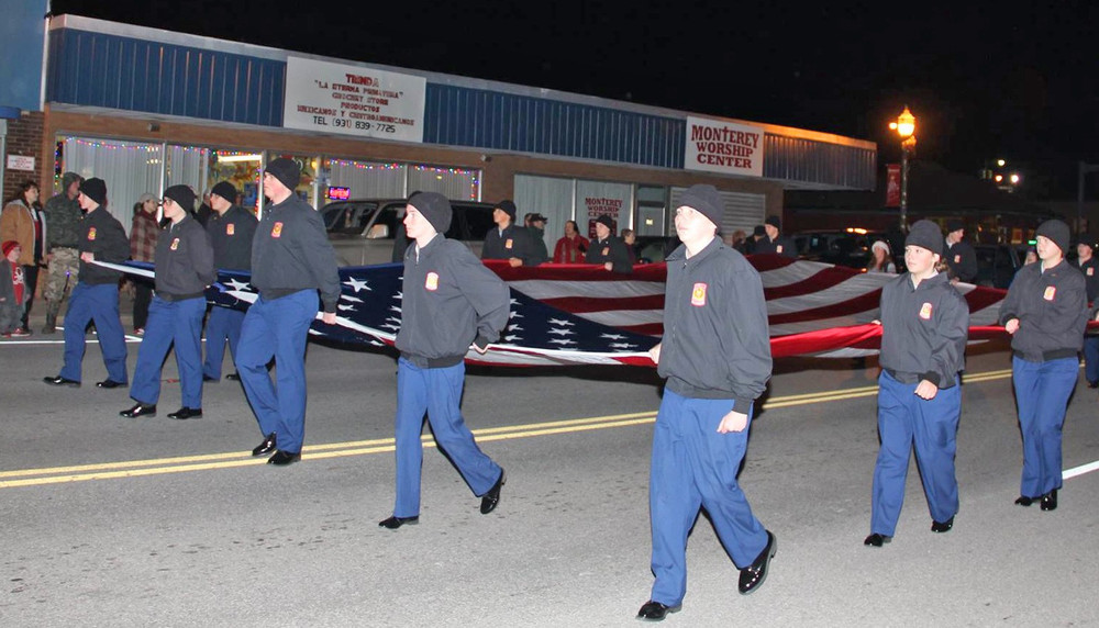 Members of the Clarkrange JROTC carry a huge American flag during the Monterey Christmas parade Saturday night.