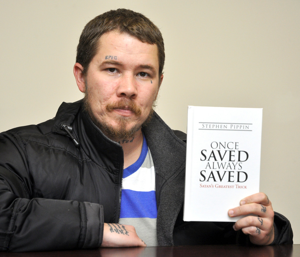 "Stephen Pippin shows a copy of his new book, ""Once Saved, Always Saved: Satan's Greatest Trick."""