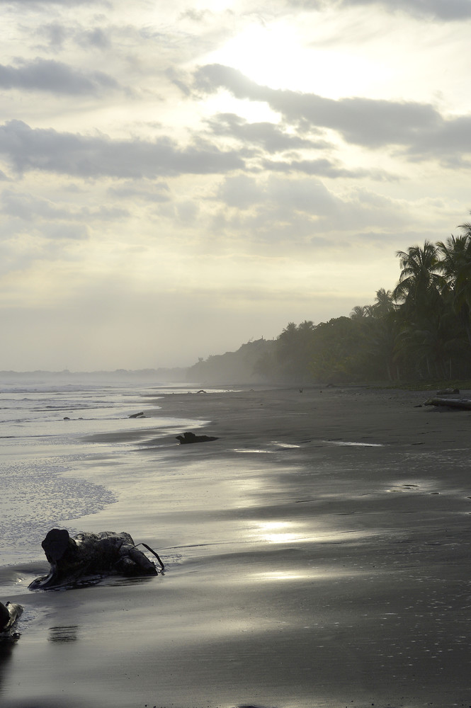 The waves roll in on a foggy beach at sunset on a beach in Costa Rica.