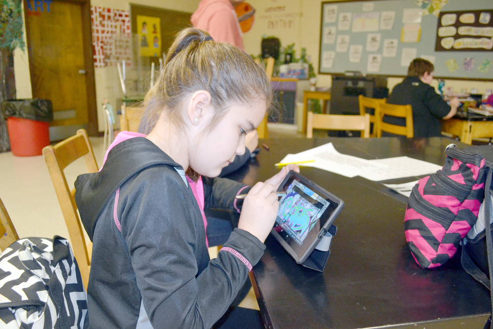 Sixth-grade student Aaliyah Servo uses a paintbrush stylus to design interactive three-dimensional graffiti on a grant-funded tablet in the classroom of Avery Trace Middle School art teacher Rhyan McReynolds.