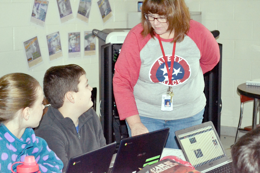 ATMS teacher Kelli Locklear, above, works with fifth grade students Sydney Beth Suits and Luke Johnson on an argumentative essay on the most vital invention to humanity. Locklear's advanced language arts students were able to use a classroom set of Google Chromebooks for researching ideas for their essays. The assignment is part of the effort to make ATMS an IB Middle Years Programme.