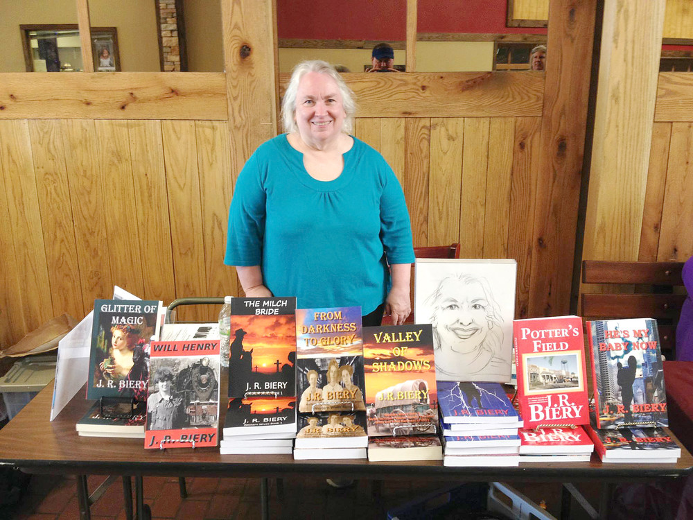 Janet Biery stands with a few of her books.