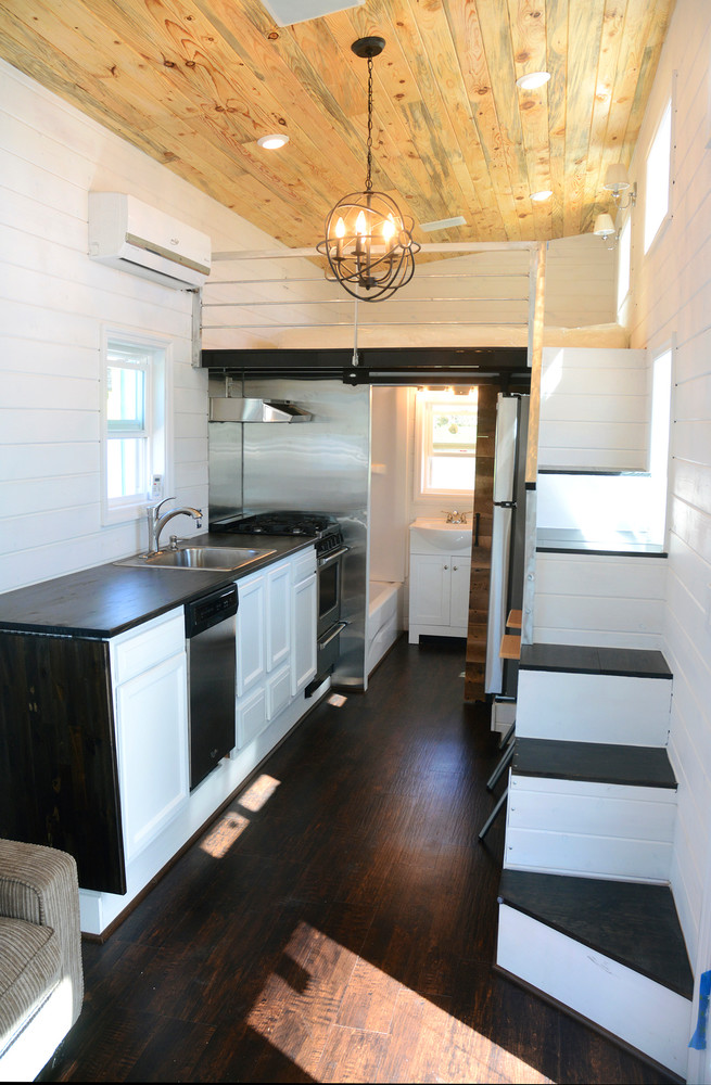 The tiny house features a kitchen, bathroom with a rolling barn door, and an upstairs with space enough for a king size bed.