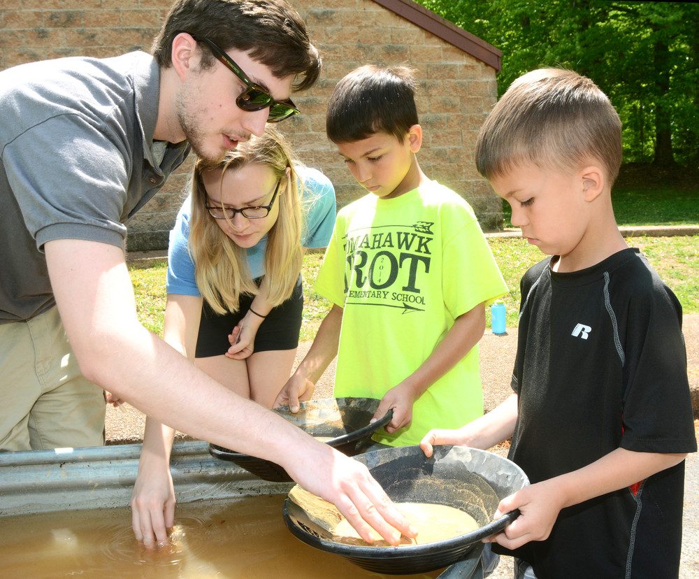 From left, Kenny Wolf and Hannah Blaylock with the TTU Geology Club, show eight-year-old Bradyn Bos and six-year-old Jadyn Bos how to pan for gold at Nature Fest.