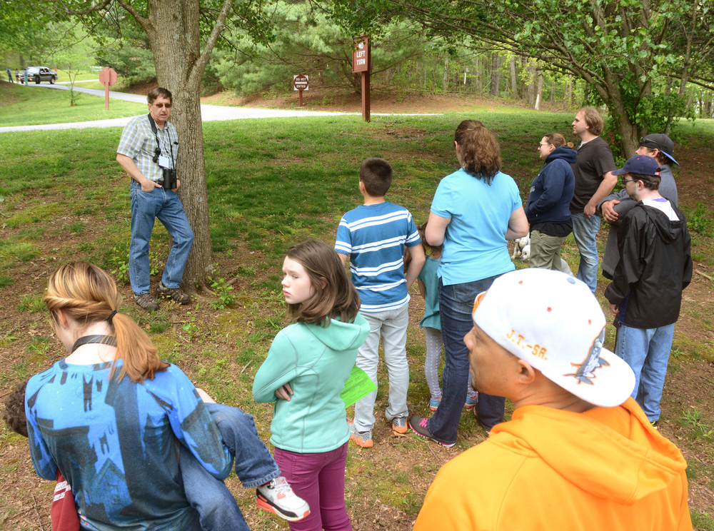 Dan Combs discusses the risk of Bradford pear trees as he leans against one in Cane Creek Park during the Tree Walk at Nature Fest.