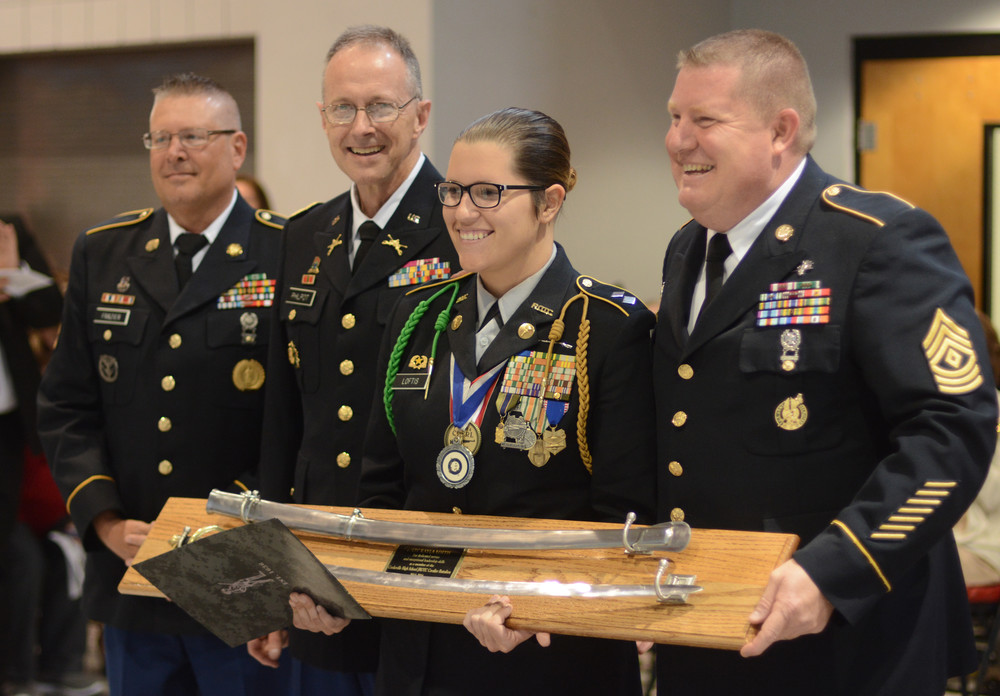Cookeville High School JROTC Cadet Lt. Col. Kayla Loftis accepts the JROTC Cavalier Battalion Saber Award from, from left, retired Sgt. 1st Class David Frazier, retired Col. Nickey Philpot and, after Loftis, retired 1st Sgt. Doug Romero.