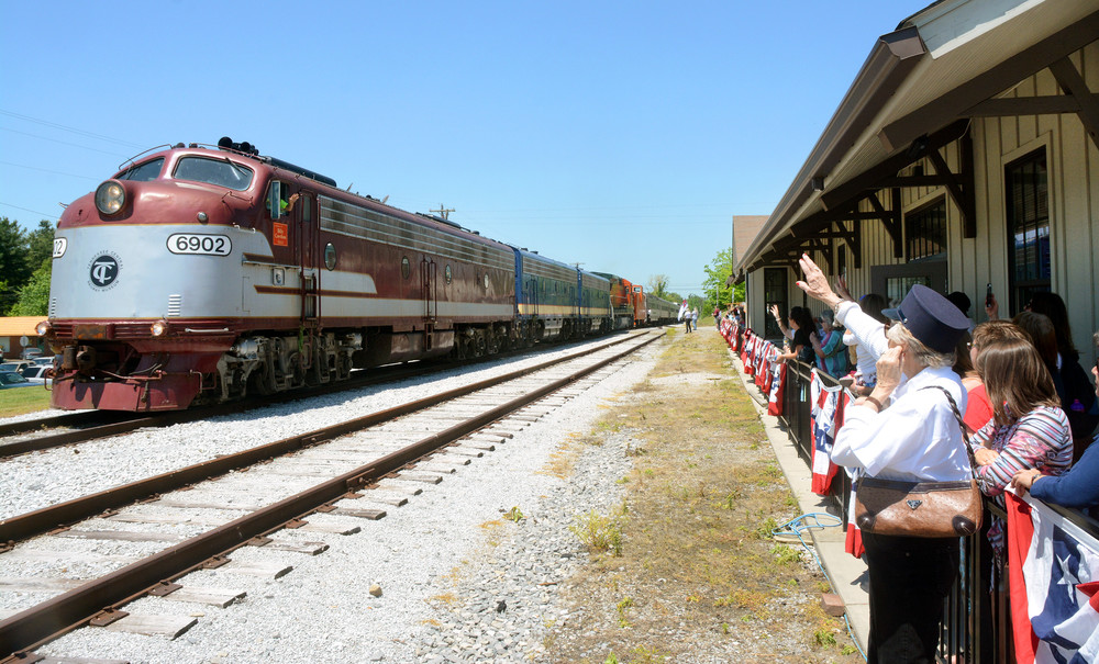 People lined up at the station wave to the conductor as the train pulls into the station.