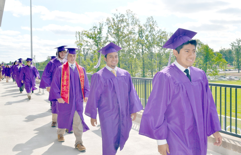 Monterey High School graduates, from front to back, Alex Perez, Elvis Perez, Jesse Raines and Zeb Randolph make their way toward a gym full of family and friends for Saturday's commencement ceremony.