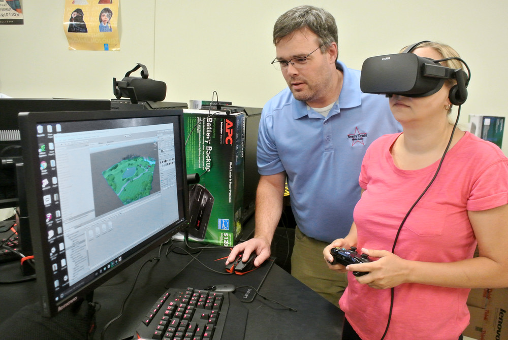Beau DeBord, design and technology teacher at Avery Trace Middle, looks at new Oculus Rift virtual reality hardware with Kim Eller, STEM teacher at White County High School, during a training session at Tennessee Tech University's STEM Center.