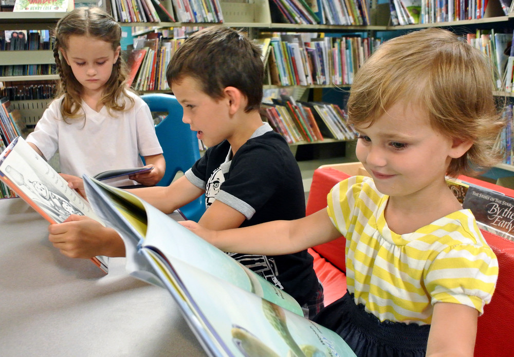Enjoying their summer reading at the Putnam County Library are, from left, Brightyn Iverson, 5, Nolan Iverson, 7, and Irelyn Iverson, 3.