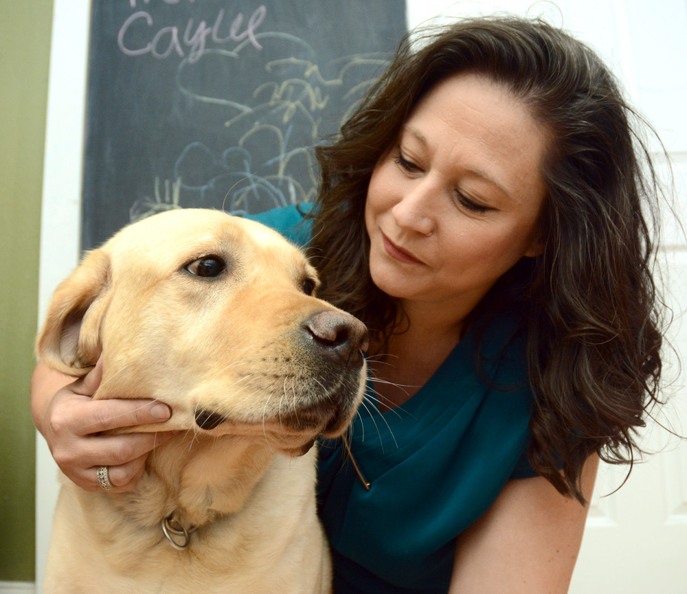 Murch, a service dog who comforts victims of severe child abuse, gets a cuddle from handler Jennifer Wilkerson.