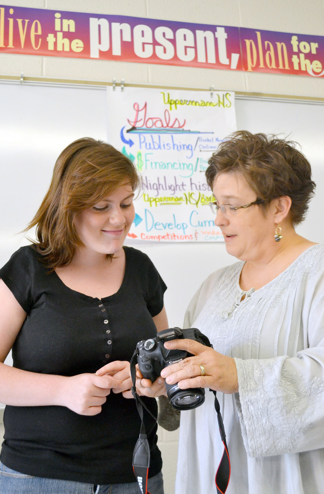 Student-journalist Stephanie Maxwell prepares to take photos for Upperman High School's newspaper with assistance from teacher Renee Craig.