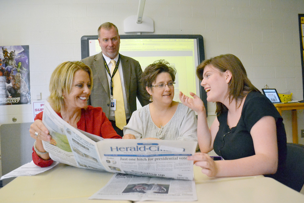 Joy McCaleb, left, mentor for Upperman High School's new student newspaper, left, shares her love of journalism with teacher Renee Craig, center, student Stephanie Maxwell and principal Billy Stepp.