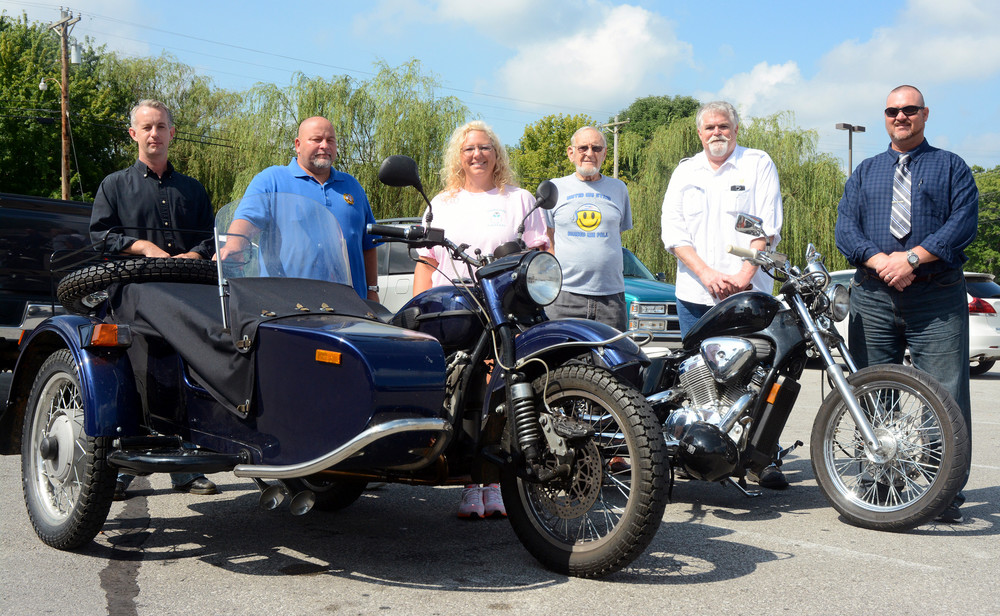 Ron Rohrbach, left, program director of Homeless Veteran Reintegration Program, gets ready for a motorcycle ride and poker run to benefit Disabled American Veterans along with DAV treasurer Neil France, DAV Transportation Coordinator Tammy Phillips, Jerry Van Horn of DAV, DAV Chapter 117 Commander Bob Hines and Tony Scionti Jr. of the DAV and employment specialist with HVRP.