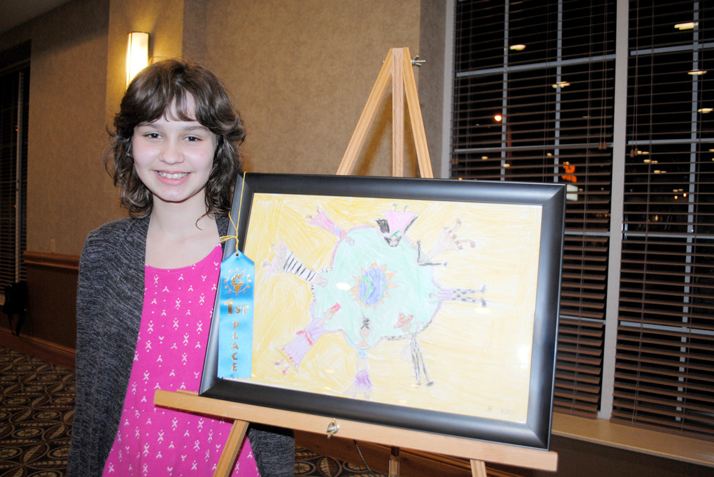 Kaylee Savage-Cutcher shows artwork she created for last year's Eyes of Diversity contest when she was a fifth-grader at Prescott South Middle School. The colorful drawing, which placed first in the middle school visual category, depicts people from different cultures in a flower-like shape, united in their diversity.