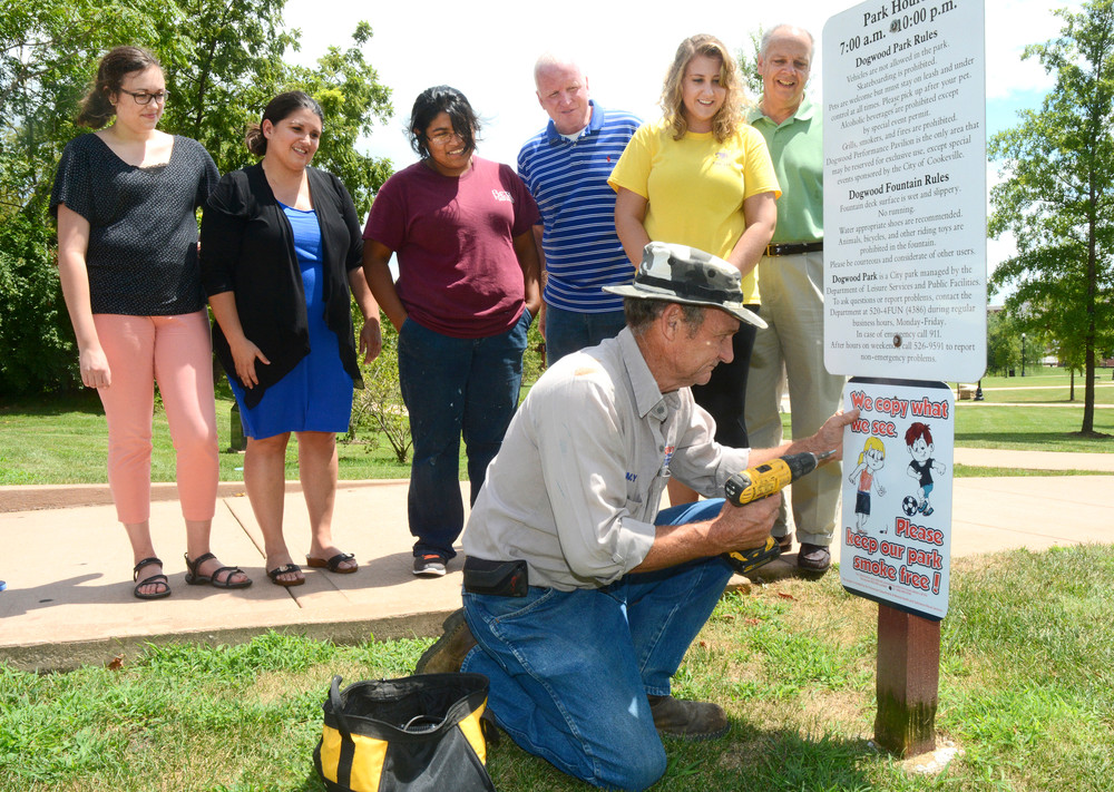 Watching as Jimmy Carmack of Cookeville Leisure Services hangs a new sign Tuesday at Dogwood Park are, from left, Abigayl Meadows, Jennifer Matthews, Isabela Ordones, Bill Gibson and Carolyn Ciotti, all of Power of Putnam, and Rick Woods, Leisure Services director. The signs are aimed at discouraging smoking.