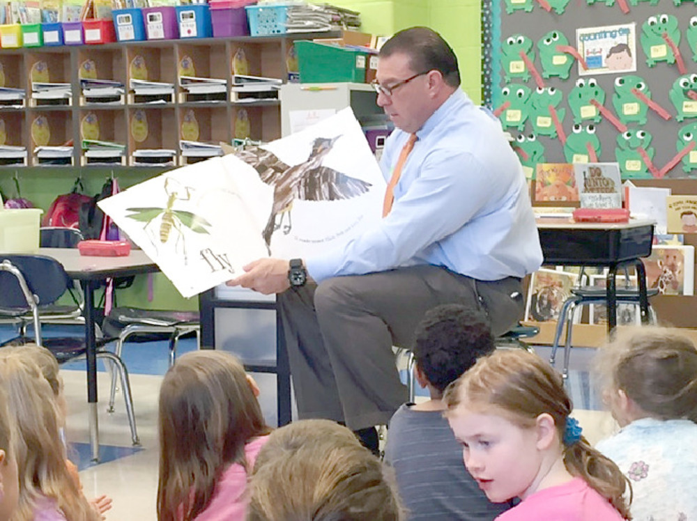 Putnam County Sheriff Eddie Farris reads with Leslie Mullican's first graders at Prescott South Elementary School. .