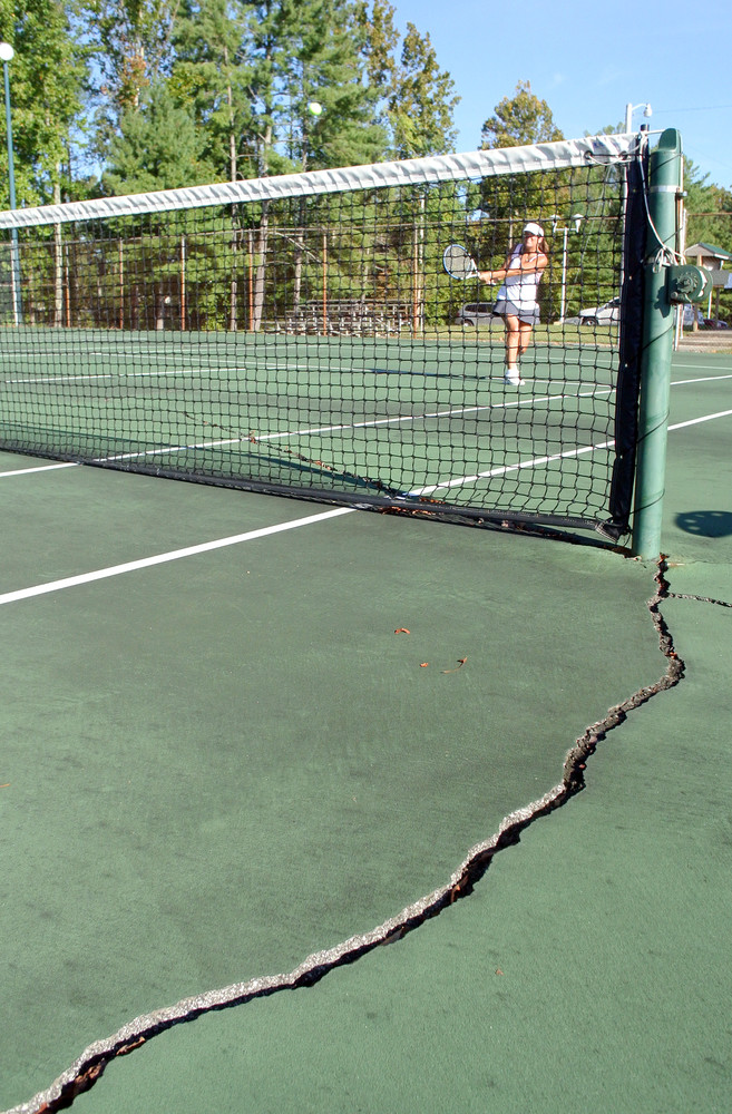 Gaye Ann Hill plays tennis Tuesday morning on one of the Cookeville Community Center courts that needs repair.