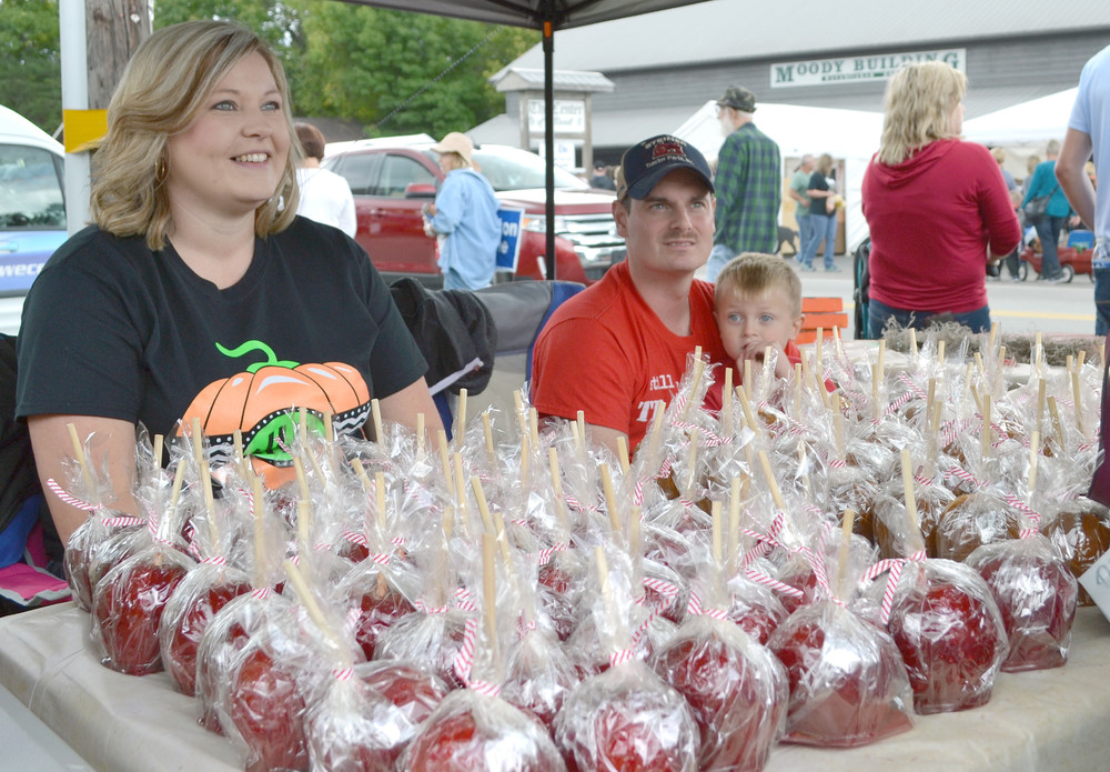 Wendy Hancock of Allardt offers candied apples to festival-goers, along with her husband, Brandon, and son Shane, who's almost 4. The Allardt Great Pumpkin Festival and weigh-off marked its 25th anniversary Saturday in Fentress County with enormous pumpkins, watermelons and green squash, as well as baked goods and numerous craft vendors. The all-day event also featured an auto and cycle show, antique tractors, music, costume contest, parade and fireworks.