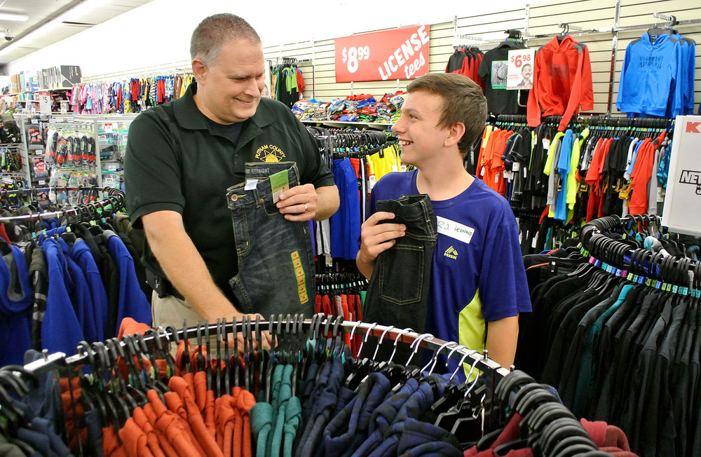 Christmastime means it's also Shop with a Cop time. Putnam County Sheriff's Deputy Casey Flatt, left, helps R.J. Leonard, 12, pick out some new clothes. Flatt is president of the Fraternal Order of Police's Cordell Hull Lodge, which sponsors the program.