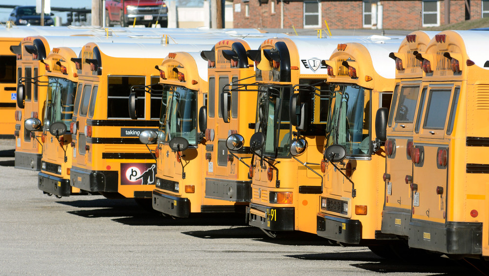 Putnam County school buses sit idle Thursday morning at the school bus lot on Veterans Drive while schools closed for sickness.