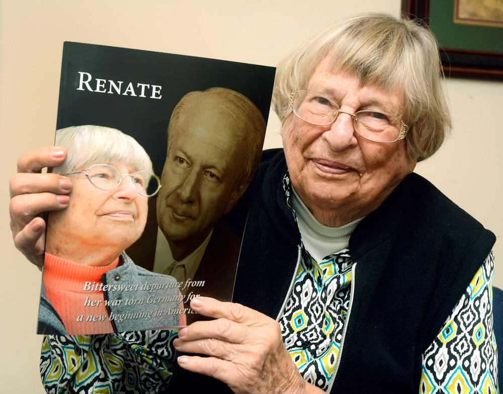 Renate Ritter holds up a copy of her book about her journey from Germany to America.