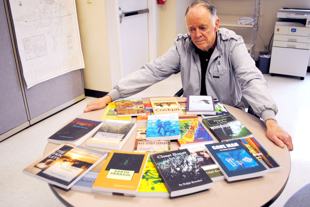 Ralph Bowden looks over a collection of his books that he's published over the years.