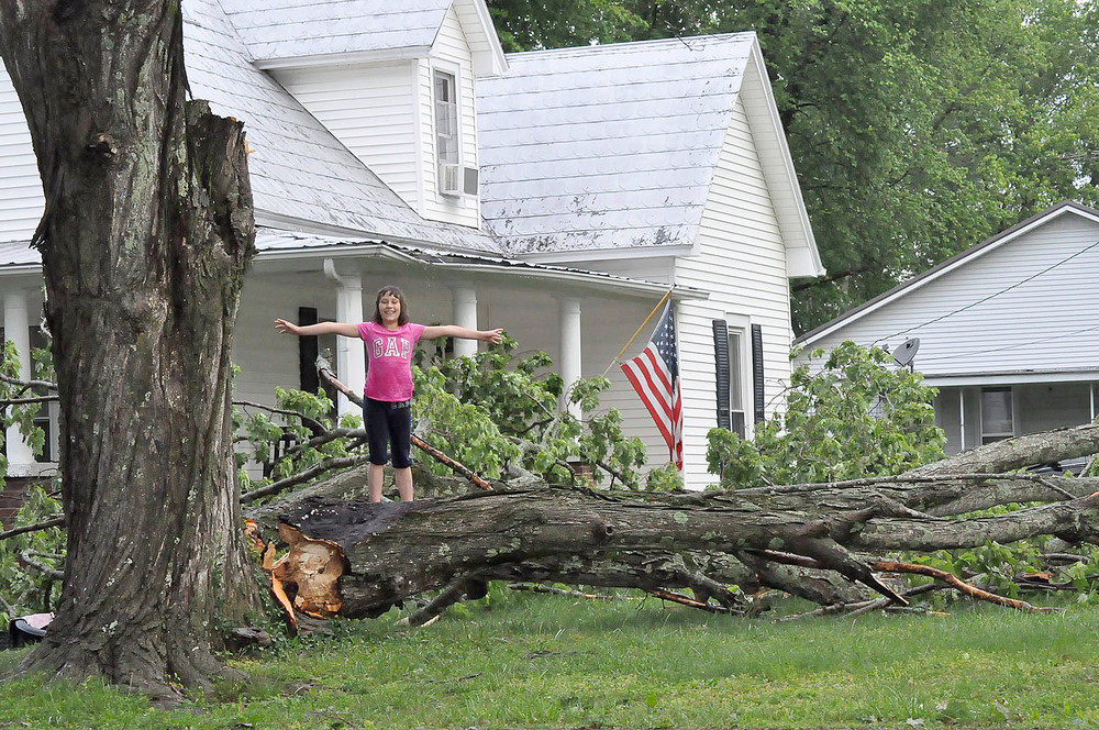 Becky Rios Morrison submitted this photo of part of an old maple tree that was blown down at her home in Algood. Her daughter, Lucy, 8, plays on the downed section. Morrison said the family was gone for the weekend and came home to this scene at the house, which was built in 1900. The fallen tree brushed the front porch gutter and and nothing else.