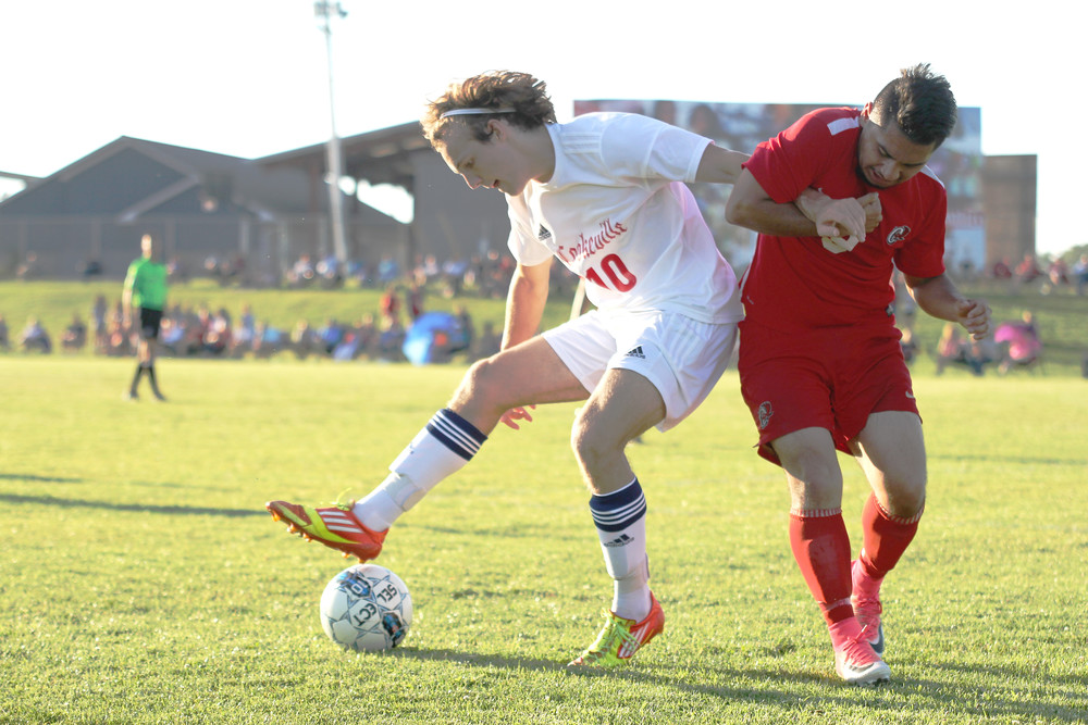 Cookeville's Darius Davis, left, battles an Ooltewah defender for a loose ball during action Tuesday night in the Region 4, 3A semifinals in Cookeville. The Cavaliers won the match 4-0 and are scheduled to play Cleveland Thursday in the regional championship.