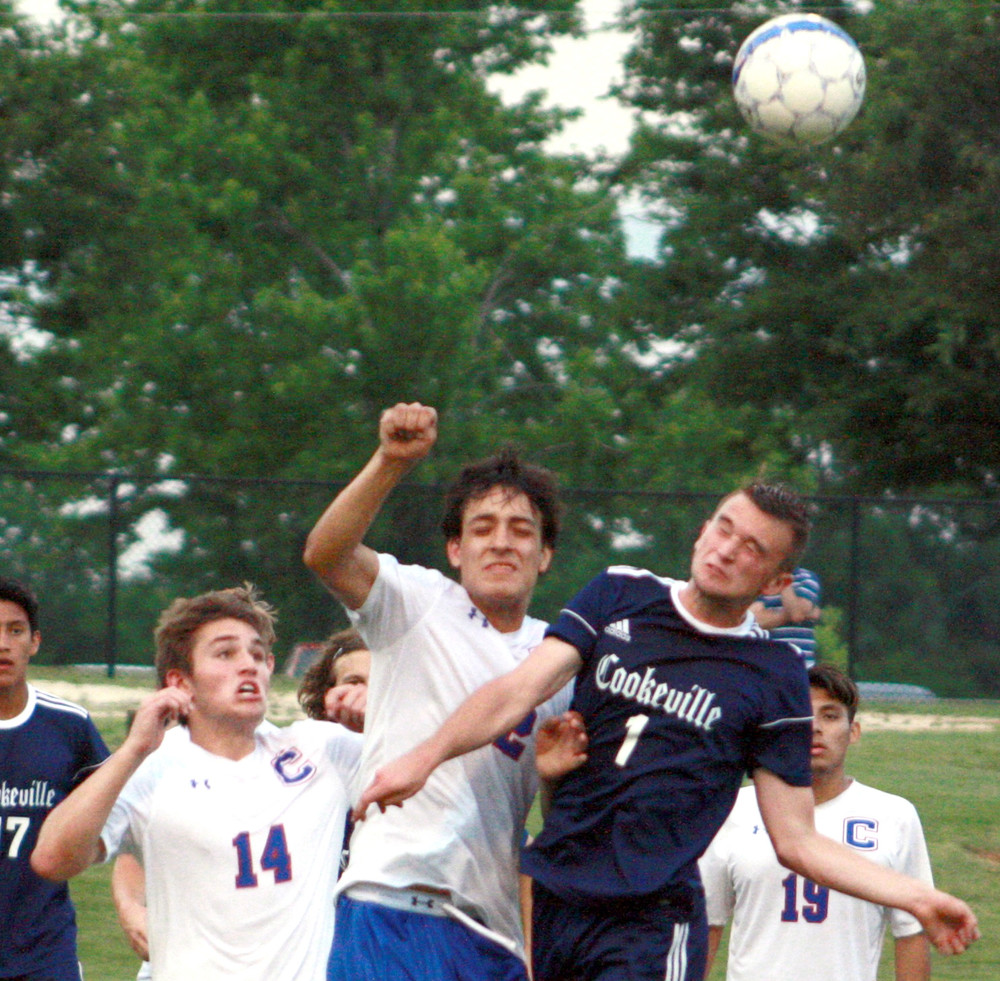 Cookeville's Bralen Clouse, right, fights with two Cleveland defenders to get his head on the ball during the Cavs' 2-0 loss to the Blue Raiders on Thursday in Cleveland.