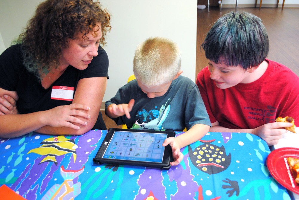 Sarah Crawford Tucker, above, watches her sons, Riley, 5, and Aidan, 13, design a new scene in a story board using a PBS kids tablet.