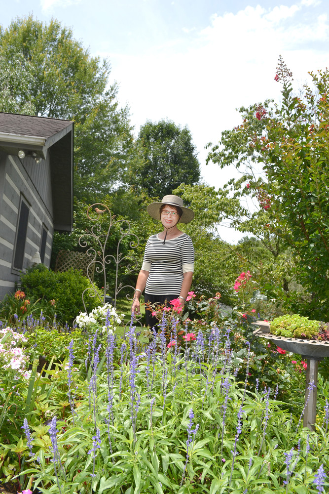 Master Gardener Mickie Loyd stands in her gardens at her home off Burgess Falls Road.