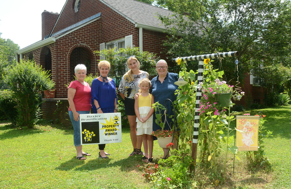 The home of Michael and Kathleen Gilpatrick has been selected as a property award winner from the Baxter Beautification Committee for the month of July. The property is beneficial to wildlife and offers an artistic flare. From left are Sharon Watts, Jeanie Lee, and Kim Phann of the Baxter Beautification Committee; Khloe Phann, Phann's daughter; and Kathleen Gilpatrick, who owns the home along with Michael Gilpatrick.