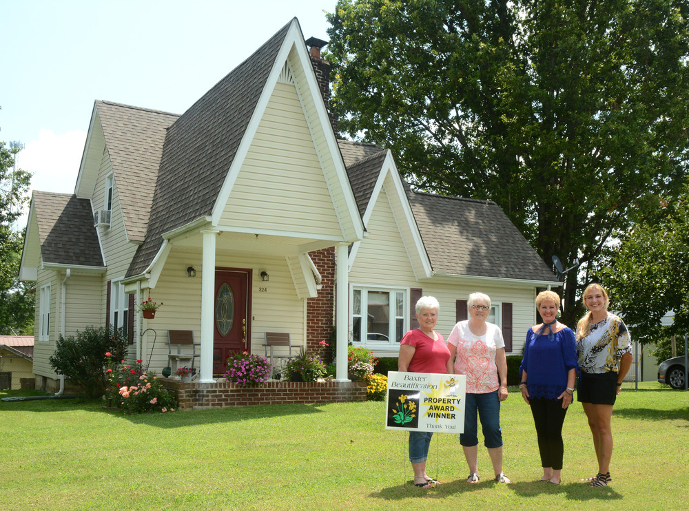 In the heart of Baxter, the home of Glenda Burgess has been named property award winner for the month of July. With impeccable landscaping, the Burgess home boasts Southern charm. From left are Sharon Watts of the Baxter Beautification Committee; Glenda Burgess, homeowner; Jeanie Lee and Kim Phann of the Baxter Beautification Committee.