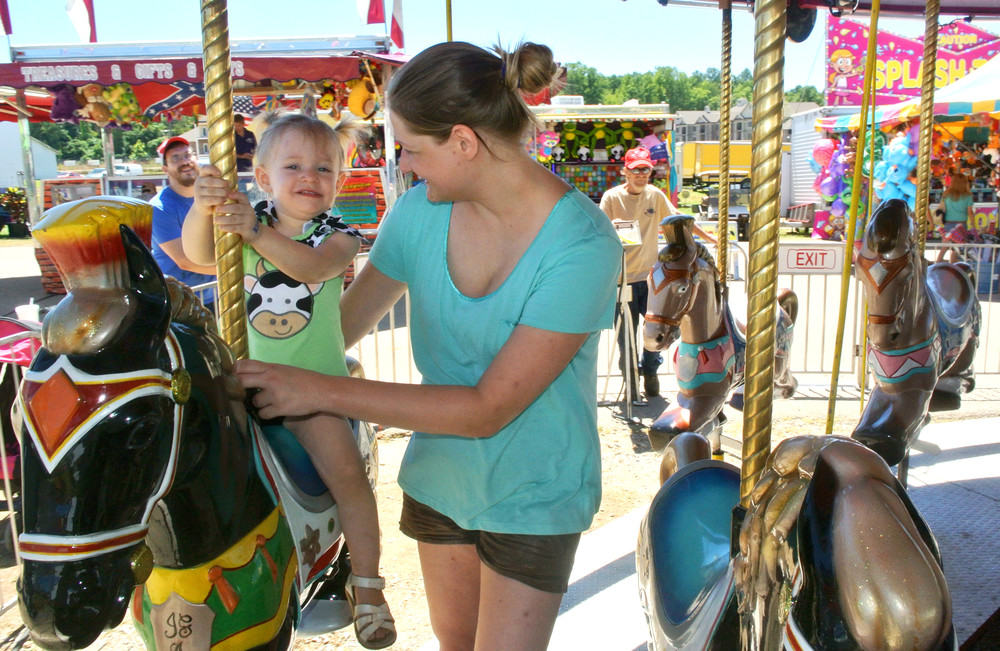Two-year-old Makenna Birman enjoys the merry-go-round with her mother, Rebecca's help during the Putnam County Fair Saturday. A new herding dogs demo is set for 6 and 8 p.m., the photography exhibit at 6:30 p.m., and also at the same time wild mule/horse show in the east arena and the mule, pony and pony mule pulling, draft horse and mule show in the main arena.