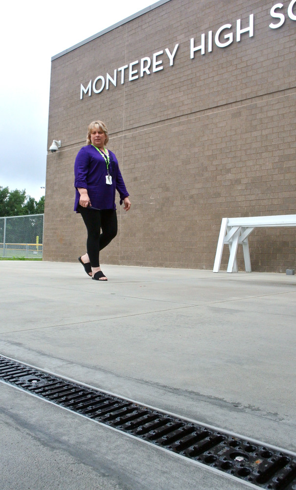 Monterey High School Principal Sonja Farley looks at a new drain that was installed to keep water from running into the school.