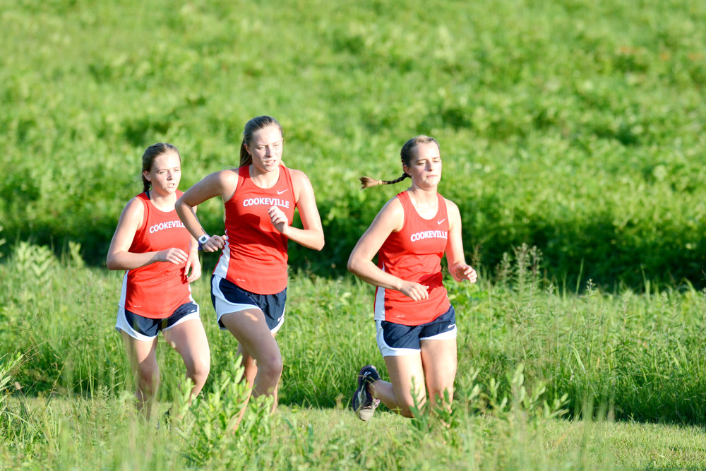 Cookeville High School runners (from left) Maddie Long, Morgan Long, and Emma Cate Jones stick together during the first lap of the MSCCA Jamboree held at CHS on Thursday.